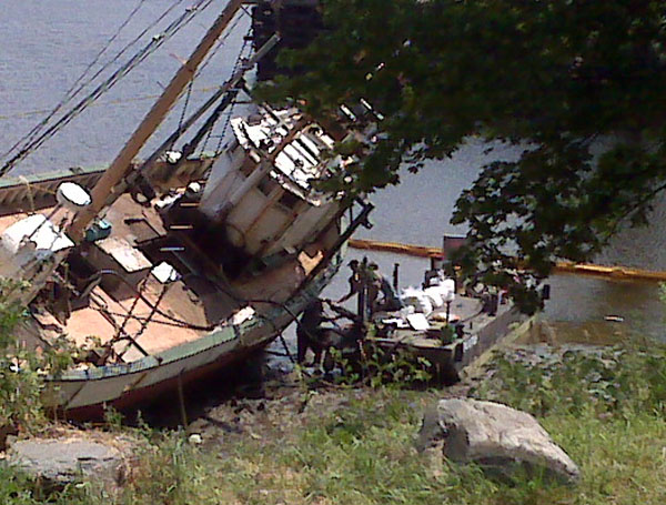 The owner of this rusty 57-foot fishing vessel, which sits on a Hampden mudflat near the Bangor town line, and Department of Environmental Protection crews work Friday morning to install air bags that are designed to make the boat float when the tide comes in Friday afternoon. The Eastern Star, which was formerly named the Roamer, sank in January while parked at the Rockland pier and ran aground Wednesday night, July 20, 2011, in a small cove near Hampden's Waterfront Marine.
