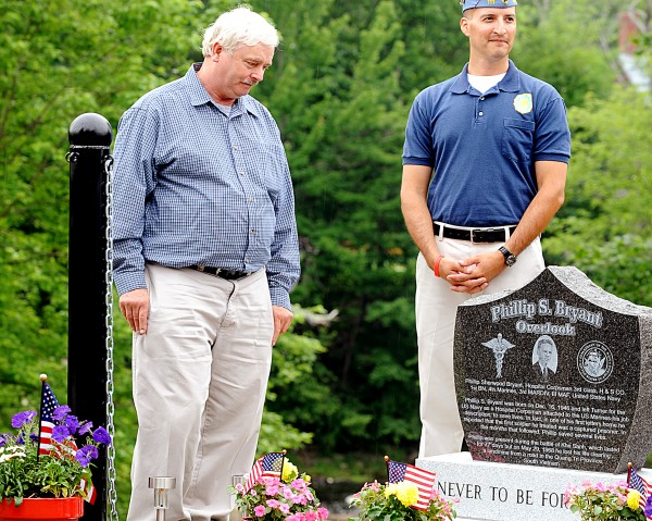 Marsh Bryant (left) looks down at the memorial to his brother, Phillip, who was killed in 1968 in Vietnam, during a dedication ceremony on Sunday in Turner. Mike Chavez (right), commander of the Sons of the American Legion Squadron 111, assisted in the unveiling.