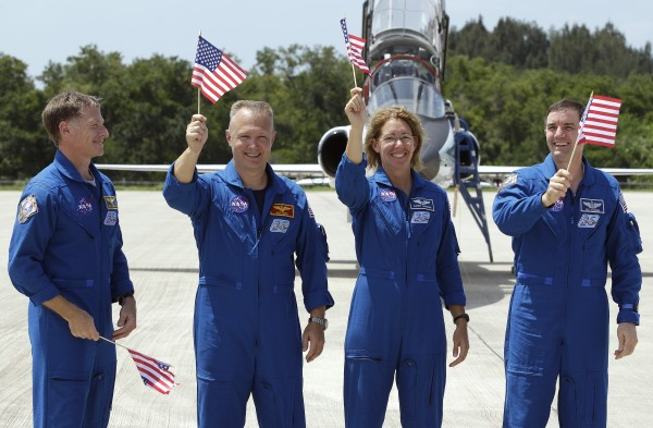 STS-135 commander Chris Ferguson, left, looks on as fellow crew members, from left, pilot Doug Hurley, mission specialist Sandy Magnus, and mission specialist Rex Walheim, wave American flags after arriving at the Kennedy Space Center in Cape Canaveral, Fla., Monday, July 4, 2011.  Space shuttle Atlantis, and her crew of four astronauts, is scheduled to lift off Friday morning on an 12-day mission to the international space station.  The launch will bring an end to NASA's shuttle program.
