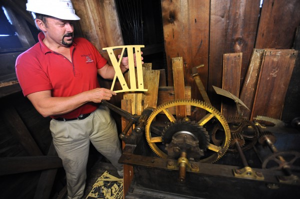 Karl Ward, President and CEO of Nickerson and O'Day, Inc holds up the Roman numeral 12 that was removed from the church clock and will be reinstalled when the structiral work is complete. The company is renovating part of the Hammond Street Congregational Church in Bangor. The project started in April and is expected to be complete in September.  The work involves fixing structural and cosmetic problems on the building that was built in 1833.
