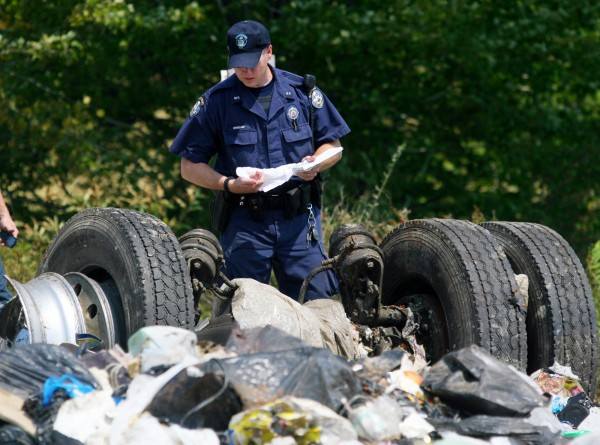 A Maine state police officer inspects the remnants of a tractor-trailer that collided with an Amtrak passenger train in North Berwick on Monday.