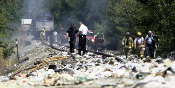 Officials survey the area around an Amtrak train that collided into a tractor-trailer Monday, July 11, 2011, in North Berwick, Maine. Both were set  on fire an official said and the truck driver was killed.