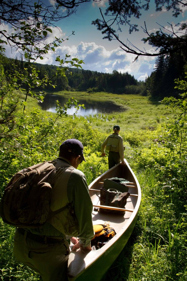 The BDN's John Holyoke and project coordinator Emily Bastian carry a canoe into a remote pond near Rangeley on Thursday during a trip to prescreen ponds that have not been formally surveyed by state fisheries officials. Maine Audubon, Trout Unlimited and the Maine Department of Inland Fisheries and Wildlife are cooperating on a project for volunteer anglers to visit and document what they find at some of  the 187 western Maine ponds.