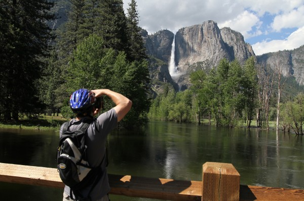 The rising Merced River and Yosemite Falls makes a scenic photo for a visitor on June, 13, 2011. Tourism was down in 2011, through June 30, at some of the country's most traditionally popular national parks.