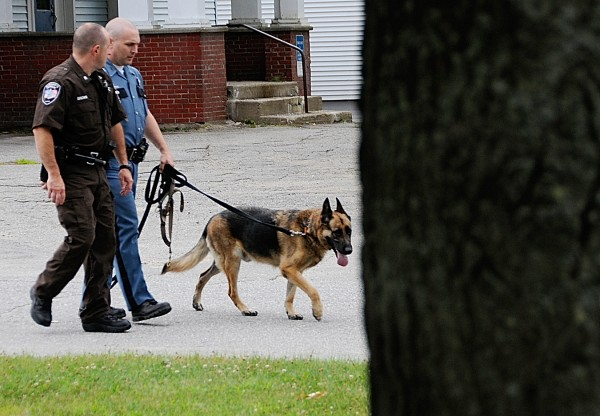With the help of a police canine, Waldo County Sheriffs Sgt. Dale Brown, left, and Maine State Trooper Shawn D. Porter search the perimeter of Down East Credit Union in Unity following Friday afternoon's robbery there. The suspect took off on foot.  At 4 p.m. when this photo was taken, the suspect remained at large.