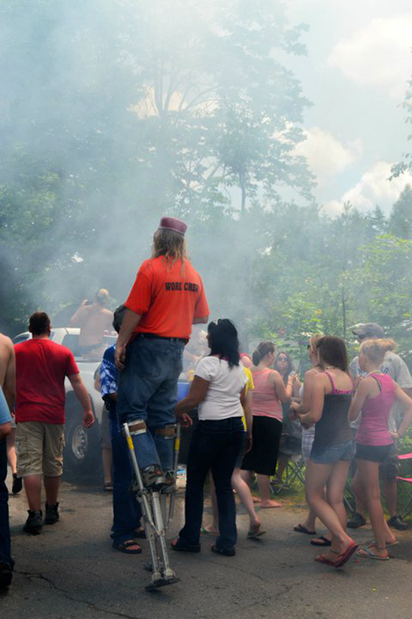 "Spectators watch as tires burn at the West Athens parade on Monday, July 4, 2011. The parade's organizer, Anna Freeman of West Athens, said Monday's parade was ""chaos."" State police said as many as 20 people got in a fight and one person was hospitalized."