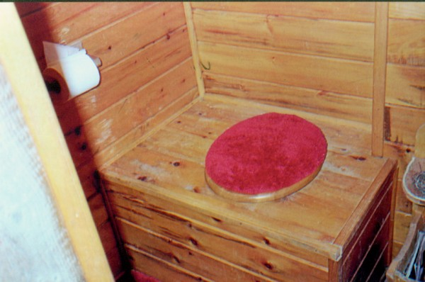 We purchased our camp with outhouse some thirty years ago on the Upper Narrows of Cold Stream Pond. One of the first projects was to panel with pine the entire inside of the outhouse. Afterwards I built a fine vanity table and chair for those that may want to freshen up on the way out. Additionally, there is ample reading material provided for those that might like to linger a while. There are two windows, one on the North side and one on the South which allow excellent cross-ventilation and which I think it necessary in an outhouse, don't you?