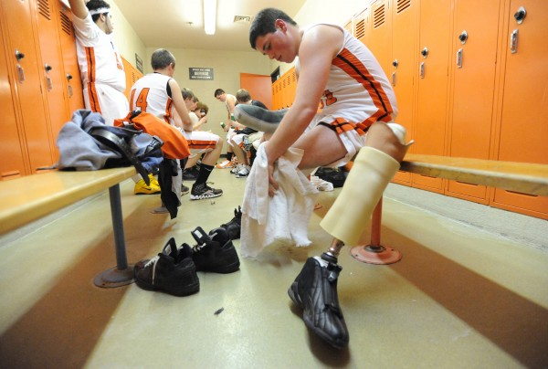 """Amputee Athlete"" is the third place photo in the Portrait-Profile category in Class I of the 2011 New England Associated Press News Executives Association contest. In this photo, Limestone Community School junior Zach Cote, 16, wipes down his leg before reattaching his prosthesis at halftime in the team's locker room during a preseason home game against Presque Isle in November 2010."