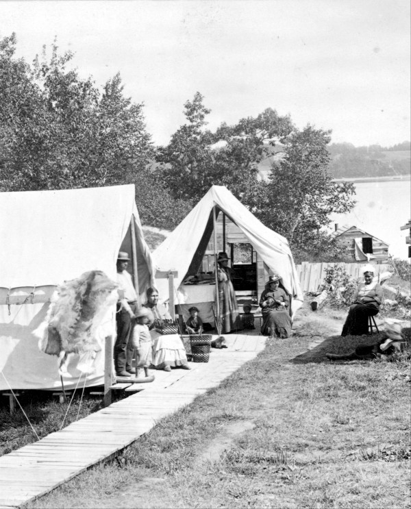 Part of the Bar Harbor Indian village, ca. 1889, when the Wabanaki encampment was situated near Eddy Brook outlet between the shore and Eden Street. Indian families set up their sale tents and living quarters here during the summers of 1887-89. A boardwalk ran from Eden Street behind Ells' Store and along the row of canvas tents that extended towards the shore.