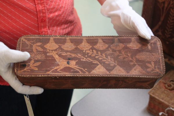 Abbe Museum Curator of Collections Julia Clark holds a birch bark glove box from the late 1800s or early 1900s.