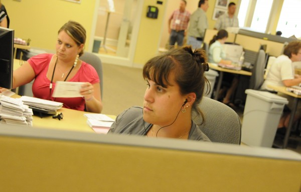 Holly Kinniery (center) of Hope and Kristi Abbott of Searsmont, both remittance and imaging processing representatives, help process claims at athenahealth's offices in Belfast on Thursday, July 14, 2011. Approximately 350 employees work at Massachusetts-based athenahealth's offices in Belfast.