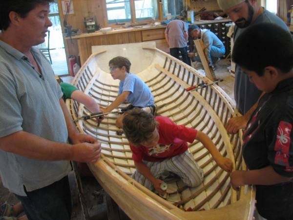 Colin Harrison, at rear, and Patrick Mocarsky work on Friday, July 29, 2011, inside an unfinished skiff under construction at Islesford Boatworks on Little Cranberry Island. The 11-foot skiff, designed by the late boatbuilder Arthur &quotChummy&quot Smith, will be the sixth boat produced by the seasonal school since it was founded in 2006.