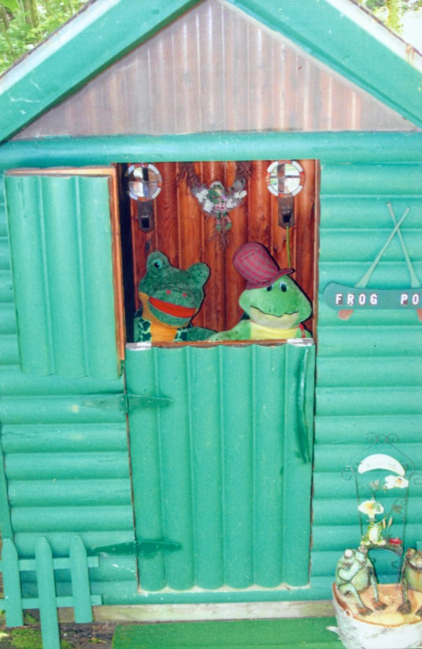 Conrad and Yolanda Bulley of MIllinocket say their two-hole Frog Pond outhouse is an original, it's attractive, comfortable and easy to maintain. The Dutch door eliminates the need for a window and provides plenty of light. The green stain, the style and variety of frog accessories, make for a pleasant visual experience. Regular lime treatments and multiple fine potpourri offerings, coupled with a discreet ventilation system provide enjoyable olfactory use in the facility. And facility is a never-needs-to-be-emptied comfort station. The hole was excavated by a backhoe and was 6 feet deep so don't fall in, they advise. On top of all that, the Frog Pond has one of the best cell phone reception signals in the area of Ambajejus Lake.