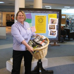 """Librarian Ann Filley with some of the door prizes (books, of course) for entering the Summer Reading Program for Adults at the Camden Public Library. The bulletin board for readers' responses is a popular feature of the summer reading program for adults. """"Why should kids have all the fun?"""" says Filley."""