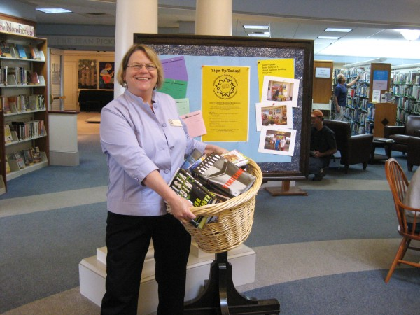"Librarian Ann Filley with some of the door prizes (books, of course) for entering the Summer Reading Program for Adults at the Camden Public Library. The bulletin board for readers' responses is a popular feature of the summer reading program for adults. ""Why should kids have all the fun?"" says Filley."