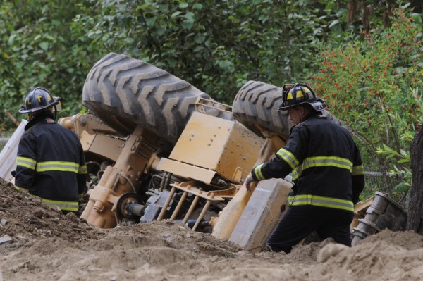 Bangor firefighters inspect the scene of an excavator rollover on the Odlin Road in Bangor on Wednesday, July 27, 2011. One person has died as a result of the accident.