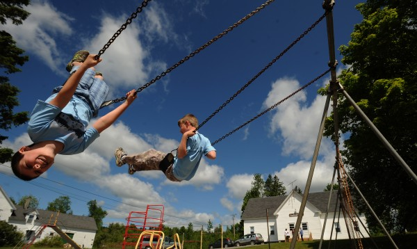 Second-grader Dean Lazore (left), 8, and third-grader Ian Blackstone, 9, swing at the playground of the Shirley Elementary School during recess. The two boys are the only pupils at the school, which has had declining student enrollment and will close this year. They spent the last day of the school year visiting Greenville Elementary School, where they will continue their studies.