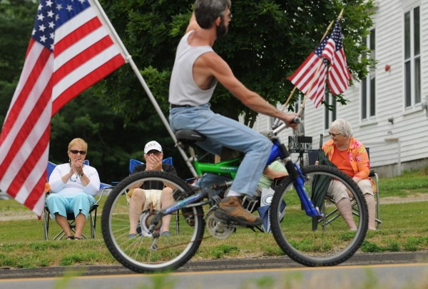 People lining the side of Route 9 in Eddington on Saturday, July 23, 2011, cheer as town selectman Charles Baker pedals his bike decorated with American flags during the parade celebrating Eddington's 200th birthday.