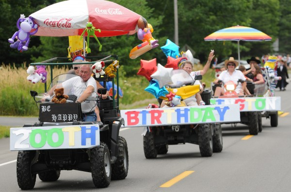 "A string of ATVs carrying signs that read, ""Happy 200th Birthday Eddington,"" form part of a parade held Saturday, July 23, 2011, along Route 9 to mark the 200th year of the town of Eddingotn."
