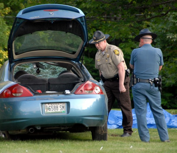 A state police trooper and a Penobscot County sheriffs deputy examine the wrecked car in which an unidentified woman was killed and an unidentified man severely injured in Enfield on Saturday, July 16, 2011.