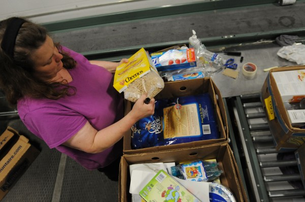 Libby Heathcoat a staff member of Good Shepherd Food-Bank inspects incoming food products at the Auburn warehouse of Good Shepard on Monday, June 27, 2011. All food coming in the doors from donated sources is hand inspected by trained inspectors to check for defects that make the product unfit for human consumption.