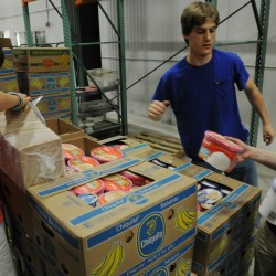 Volunteers Mitchell Berube, left, and his sister Kristen, right, both of North Yarmouth, along with Bradley Hatfield of New Glouster repack ice cream in the frozen foods section of Good Shepherd Food-Bank in Auburn on Monday, June 27, 2011. This was the first time volunteering for the Berube family who say they can't find summer work so they choose to help out at Good Shepherd, both say they like the work and will return soon.