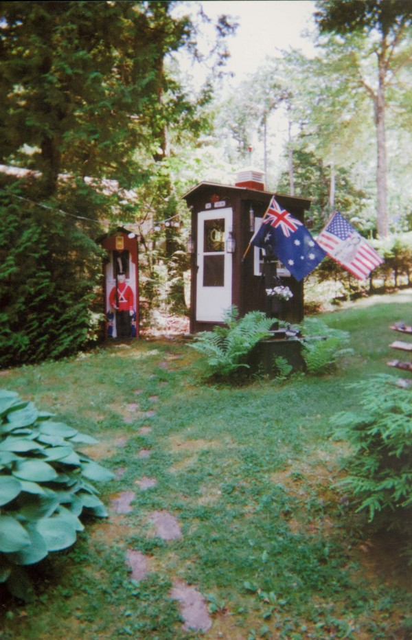"""When I was building my camp 50 years ago, said Raymond Fournier of Otis, I had a temporary outhouse made with a recycled Air Force locker from Dow Airfield in Bangor. It was so small we were forced to back in with our pants already down. Everyone made so much fun of it that I said, """"the next outhouse I build will be a classic."""" Some people refer to their outhouse as the throne, so mine is definitely one. I used an antique potty chair and cut the legs off and set it on a form that you have to step up to. Dried flowers are draped from columns with a scepter mounted within reach befitting a throne. Also a French boudoir working telephone and $100 bills toilet paper add some class. Multicolored carpet squares cover the walls. The windows are ersatz stained glass for privacy. It also is lighted with a crystal chandelier that hangs from a beamed ceiling. Electric baseboard heat maintains comfort during cold weather when the water is turned off. There is an almost life-sized queen's guard in full uniform that stands sentry duty in his own small building next to the loo. My family and friends gave me an outhouse warming when it was finished. I especially like the sign that reads """"this is a high class place, act respectable."""" For many years friends from surrounding camps would come and have their picture taken, some still do. When they come I put on my throne cap that a friend had made special for me. Many visitors have sent me photocopies of themselves sitting on the throne."""