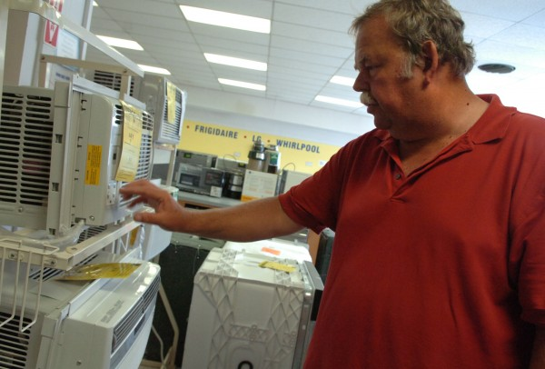 "Jack Eisentrager, owner of Dunnett Inc., demonstrates an air conditioner in the Bangor appliance store on Thursday, July 21, 2011. According to Eisentrager, the store has sold between 150 and 200 air conditioners in the past several days, with smaller models as the most popular customer choice. ""Definitely air conditioners are sold when it gets hot,"" said Eisentrager. He then concluded, ""when it's comfortable out, you don't think about buying one."""