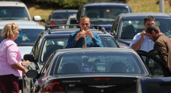 Garrett Cheney (center), along with family and friends, has lunch on the hood of a car in the parking lot of the Penobscot Judicial Center in Bangor on Wednesday, July 27, 2011, during a break in his trial in the hit-and-run death of University of Maine student Jordyn Bakley.