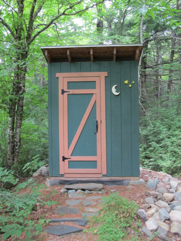 """This outhouse is the nature lover's delight. The exterior is adorned with a hand-carved moon and stars. Inside the visitor to the hallowed halls is entertained by unique items that help wile away the time. For example, a wooden grape-man (not pictured) and """"warminghut"""" license plate, both hand-carved, decorate the walls as do other interesting artifacts and relics. On a more serious note, a mason jar holds the cremated ashes of the previous outhouse along with a small photo album showing the steps of its demise. The outhouse's museum-like quality insures that each time a visitor enters, he or she will see something not noticed before. No need for a chamber pot. A motion-sensored light greets nightly"""