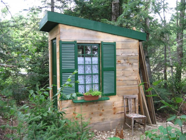 Carol Leonard of Hopkinton, N.H., sent this picture of her family's new Pooporium at Camp Kwitchabitchin on at Bad Beaver Farm, 222 Red Bridge Road, Ellsworth, that was made last spring with home-sawn lumber by her husband, Tom. The windows came from a 1920's lake house in New Hampshire that was torn down to make way for a McMansion. The door is a beautiful old solid wood door that she painted the deep dark green that I've used on all the trim. Tom decided to put a shed roof on the structure with a slight pitch to it for snow melt. She found shee had some shutters in a shed that fit the windows perfectly. She painted the shutters the same trim green and Tom put up a little plant shelf under the window that holds a crock planted by my mother. I found some elegant lace curtains in a thrift store that she hung in the windows.