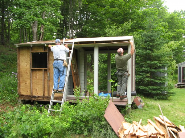 """This outhouse/studio at 1112 north Lubec Road, was a work in progress, when I read the article about an outhouse competition in the Bangor Daily news. The original building """"Wiffle Tree Manor """" was 6'by8'shed ,to which a screened porch had been added. The outhouse was a separate building. Both were in need of repair. What to do? Russell Wright of Lubec ,who did the renovation suggested why not make the shed into an outhouse Special thanks go to Brian Brody. After the round hole was cut in the floor,he dug out the 4'hole,eventually hanging head first into the hole,digging with a garden trowel into a bucket. The porch was finished with plexiglass windows and a screen door. While using this spacious outhouse, you have a three way view,windows on either side in the building or out the open door. The result of this innovative work is a twofer, a spacious outhouse and a mosquito free summer studio. Thank you Russell Wright, Brian Brody and Bud Boomer"""