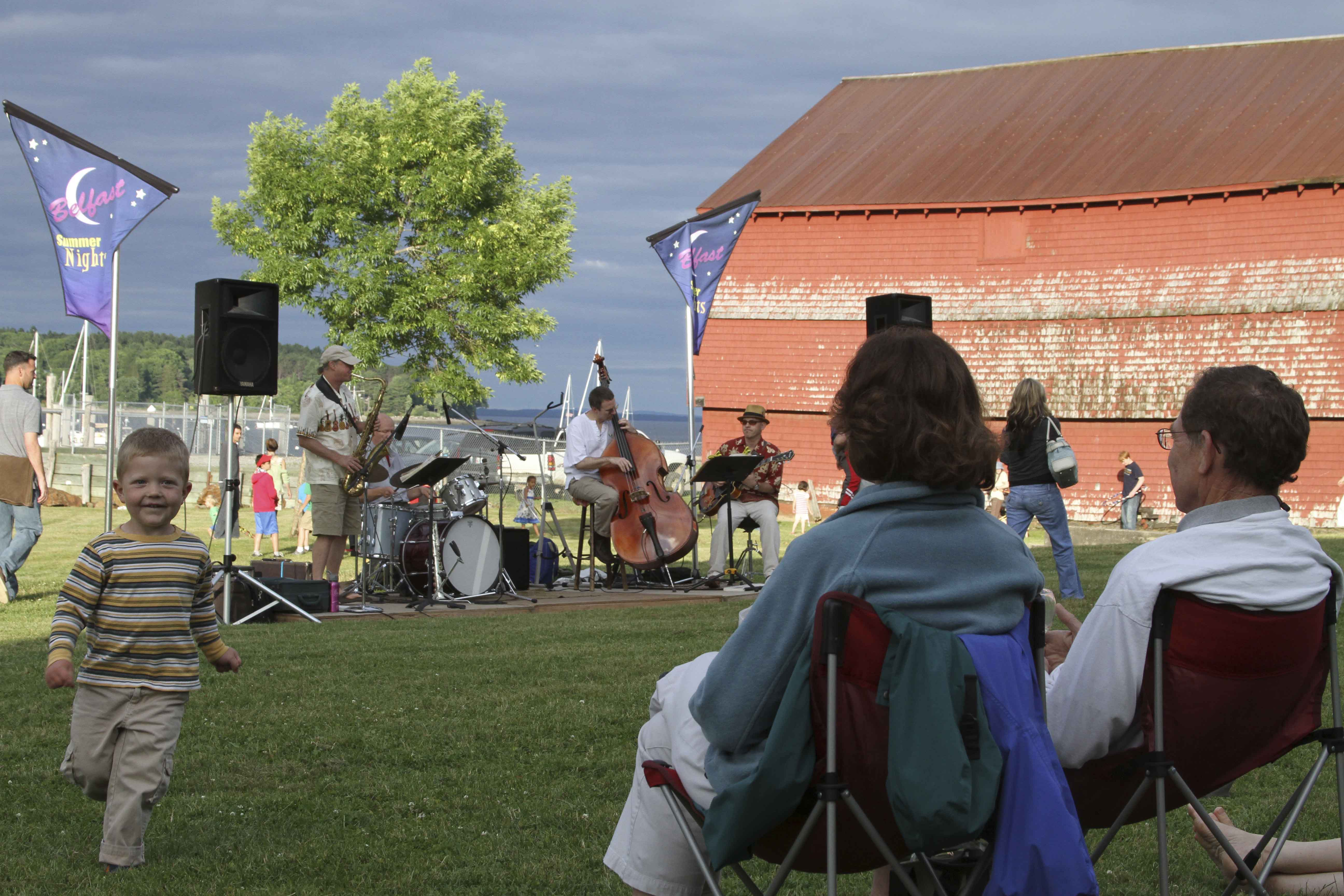 Listeners enjoy the music of the Bel Isle Trio, consisting of Bruce Boege on saxaphone, Dave Clark on guitar, Eric Davis on bass and Jeff Densmore on drums. The trio performed on June 30 at Heritage Park in Belfast as part of the city's Belfast Summer Nights series.