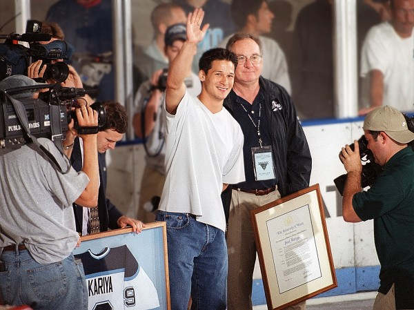 Paul Kariya, flanked by then-University of Maine President Peter Hoff,  waves to hockey fans after his No. 9 jersey was retired by the school during a ceremony at the alumni game in July 2001 at Alfond Arena.