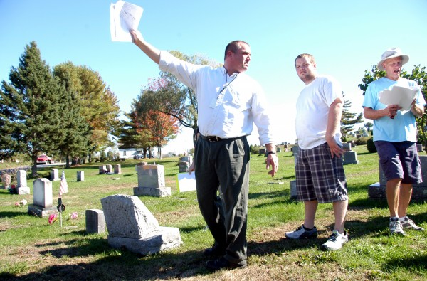 Mattanawcook Academy teacher Curt Ring (left)  lays out the remaining mapping to be done while Lincoln Cemetery, parks and Recreation Department Director Ron Weatherbee (right) checks off completed work at the West Broadway cemetery on Tuesday. A dozen RSU 67 high school students, including Darrell Savage (center), 18, of Lincoln are mapping town cemeteries as part of their service learning class.