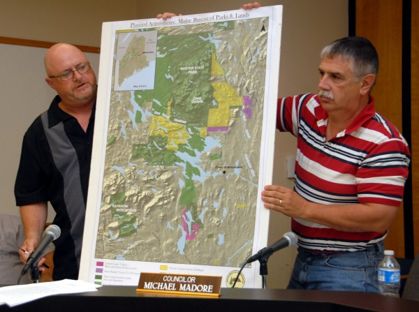 Millinocket Town Councilor John Raymond [left] speaks while