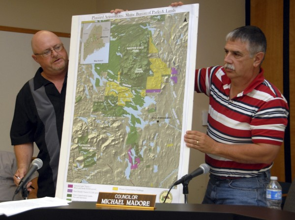 Millinocket Town Councilor John Raymond (left) speaks while Councilor Michael Madore holds a map illustrating environmentalist Roxanne Quimby's land holdings during a meeting on Thursday, July 28, 2011.