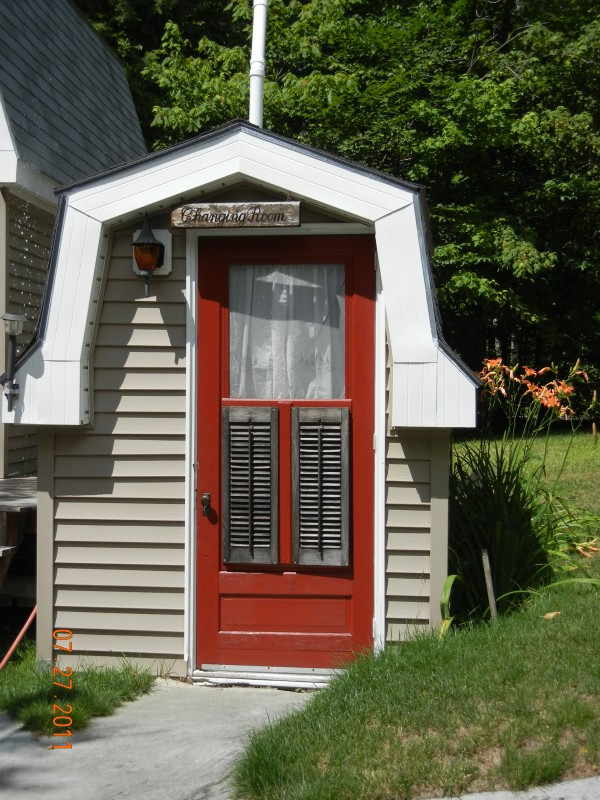 Our outhouse at Cedar Lake is complete with an antique 'throne'. And, it has a 'potty chair' insert for the grandchildren. We took an antique chair, removed the leather insert, and replace it with a toilet seat. When the grandchildren came to visit, we inserted the 'potty seat' and pushed up the sturdy step Grampy made for them to get to it.  In the first picture big sister, Baylee, takes little sister, Emma, to the 'Potty Chair Outhouse' first thing in the morning.  The second picture is the 'potty chair' throne.  And the third picture shows the outhouse, affectionately called 'The Changing Room' because many suits were put on and taken off there to keep wet, sandy clothes and feet out of the camp.