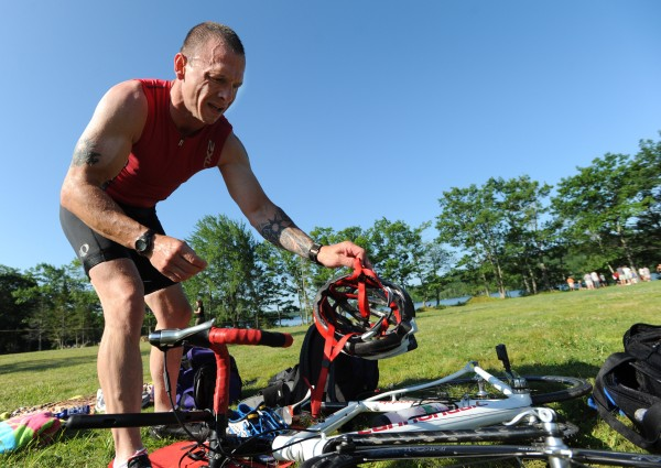 After swimming a quarter-mile and drying off, Ed Pomeroy of Bangor gets his bike gear ready to compete in the Hope Triathlon on July 16, 2011, in Hope.