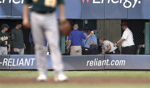 Emergency workers tend to a man who fell out of the stands while trying to catch a baseball tossed his way during a game between the Texas Rangers and the Oakland Athletics on Thursday, July 7, 2011, in Arlington, Texas. The Rangers said the fan died after the fall of about 20 feet.