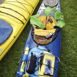 When heading out for a paddle on the ocean in a kayak there are some basic safety items you should have on you or within easy reach. Starting toward the bow (bottom of photo) and working back: a compass, bilge pump, rescue stirrup (coiled and clipped to deck bungee), a water bottle, paddle float, cell phone (in waterproof case tethered to deck bungees) spray skirt, waterproof VHF radio (sitting on spray skirt, but carried in lifejacket), lifejacket (Personal Flotation Device) and a spray jacket. The kayak should have bulkheads between the cockpit and fore and aft compartments (accessible via waterproof hatches). A sponge (clipped to aft deck bungees) comes in handy to mop up residual water in the cockpit.