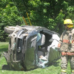 """A rescue worker stands next to a vehicle that was totaled Monday afternoon in an accident on U.S. Route 1. Clare Sullivan, 71, of Brooklin was """"conscious and alert"""" as rescue workers cut her out of her Toyota RAV4. Police think that she may have fallen asleep while driving east."""