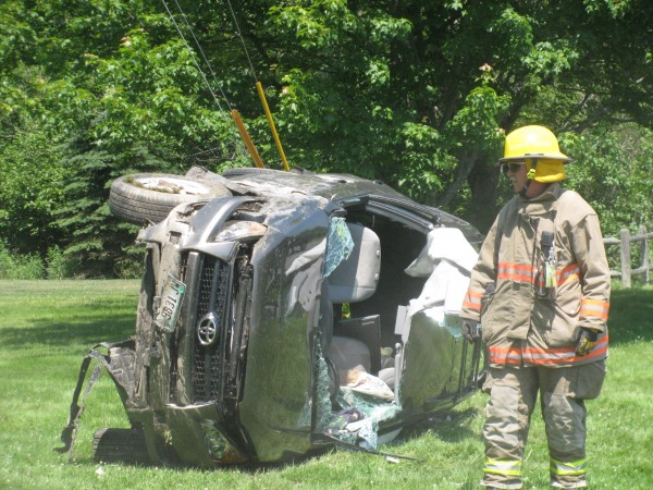 A rescue worker stands next to a vehicle that was totaled Monday afternoon in an accident on U.S. Route 1. Clare Sullivan, 71, of Brooklin was &quotconscious and alert&quot as rescue workers cut her out of her Toyota RAV4. Police think that she may have fallen asleep while driving east.