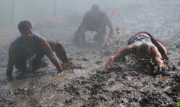 While being blasted by water from snowmaking guns, Tough Mountain Challenge racers plunge through a mudpit under barbed wire during Saturday's 3-mile event that featured 12 obstacles at Sunday River Ski Resort's South Ridge area.