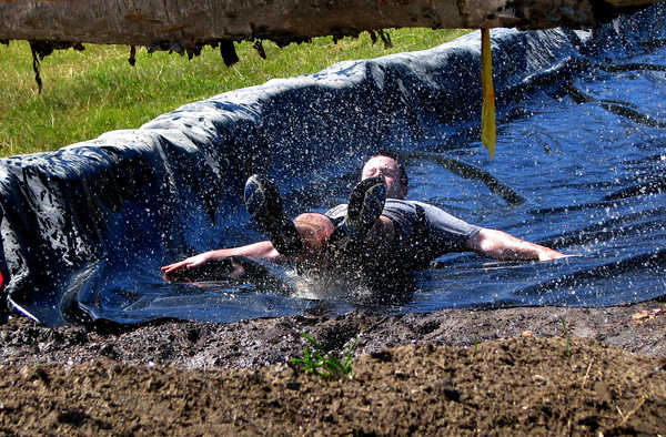 A Tough Mountain Challenge racer slides feet first down a canola oil-slicked tarpaulin toward a muddy water pit under a log during Saturday's Tough Mountain Challenge 3-mile race at Sunday River Ski Resort in Newry.