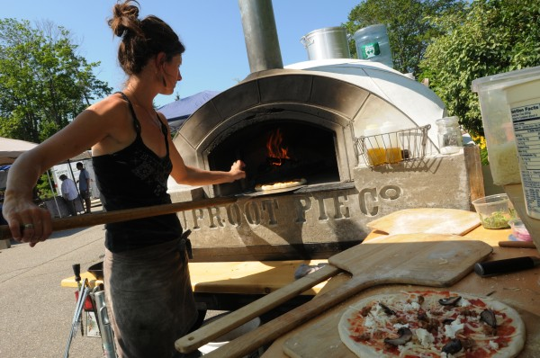 Jessica Shepard puts a pizza into her portable wood-fired pizza oven at the Camden Farmers Market on Saturday, July 16, 2011. The one-of-a-kind oven weighs close to a ton and was built by her partner who is also a sculptor.