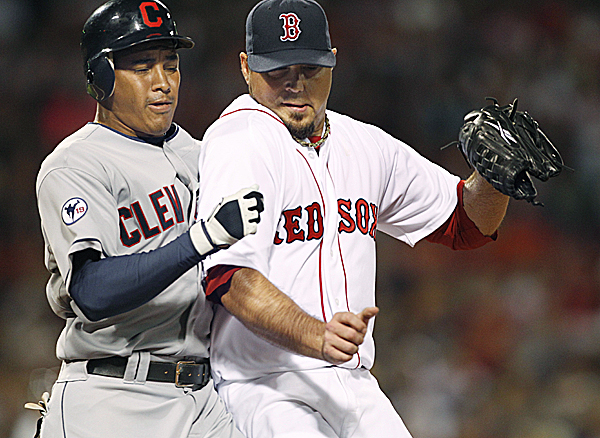 Cleveland Indians' Ezequiel Carrera bumps into Boston Red Sox starting pitcher Josh Beckett as Beckett covers first to get Carrera out on a ground ball during the second inning at Fenway Park in Boston on Tuesday night, Aug. 2, 2011.