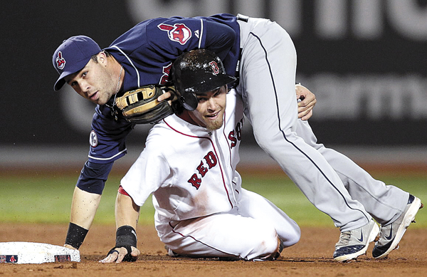Cleveland Indians second baseman Jason Kipnis falls over Boston Red Sox's Josh Reddick, who was forced out at second during the fourth inning of a baseball game at Fenway Park in Boston on Wednesday, Aug. 3, 2011. David Ortiz scored on the play.