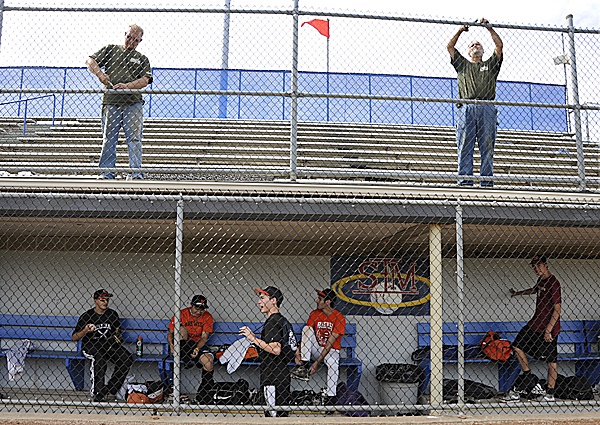 Richard Winship (top left) and George Harmon (top right), employees with Hermon-based Allenfarm Fence Co., secure new chain link fencing in the stands as the Maine District 3 champions from Brewer prep in the dugout for their practice Tuesday afternoon at Mansfield Stadium. They are getting ready for the upcoming Senior League World Series, which starts Sunday.
