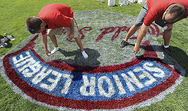 Mack Susi (left) and David Utterback work on painting the logo on the grass for the Senior League World Series at the Mansfield Stadium in Bangor Friday, August 12th 2011. The Series' opening ceremony will be held at 7 p.m. on Saturday.